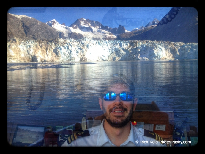 #5 Lindblad Expeditions's Chief Mate at the helm with Johns Hopkins Glacier reflecting in the window in Glacier Bay National Park, Alaska.