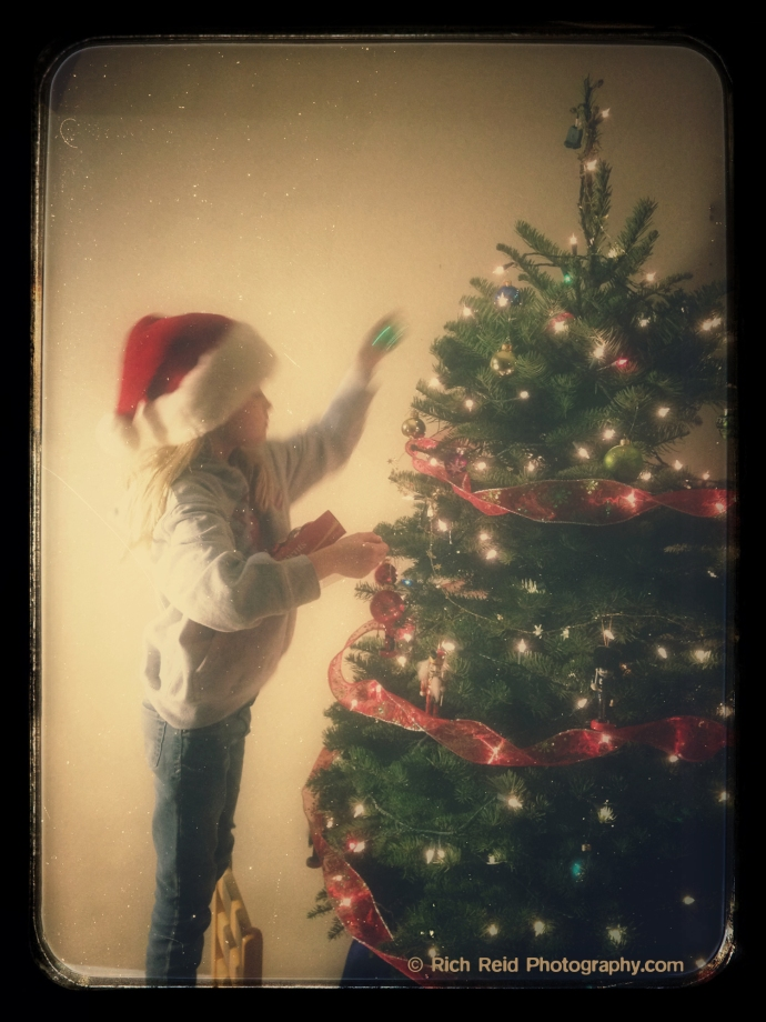 Vintage look of a girl decorating a Christmas tree.