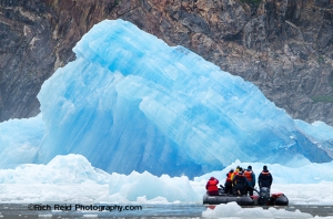 Inflatable boat near a recently calved iceberg from South Sawyer Glacier in Southeast Alaska.
