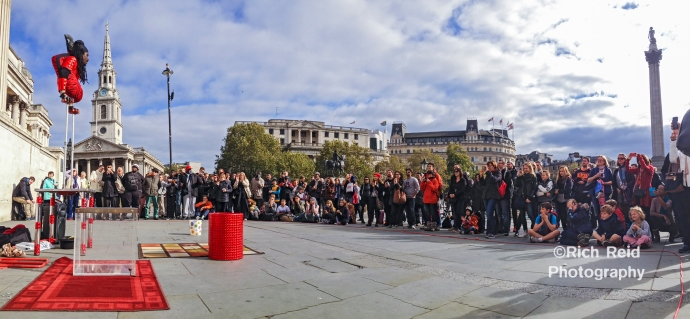 Panorama of Contortionist Yogi Laser performing for a crowd in Trafalgar Square in London, UK.